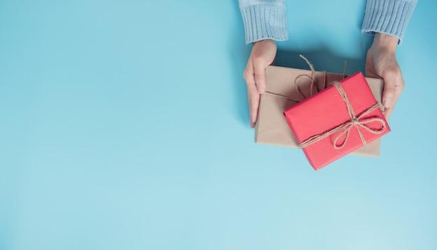 Kobiet ręki trzyma rzemiosło tapetują prezenta pudełko na błękitnej tła i kopii przestrzeni. na obecne boże narodzenie, nowy rok, walentynki lub rocznicę.