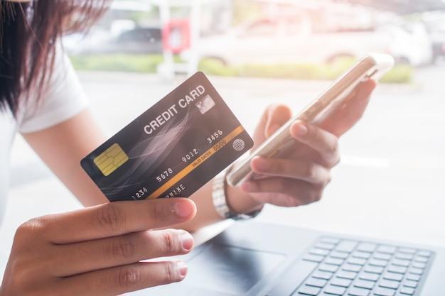 Kobiet ręki trzyma smartphone i używa kartę kredytową