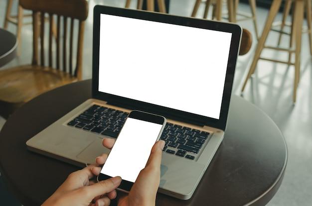 Kobiet ręki trzyma telefon komórkowego i komputeru laptop