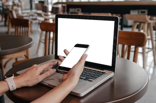 Kobiet ręki trzyma telefonu komórkowego i komputeru laptop