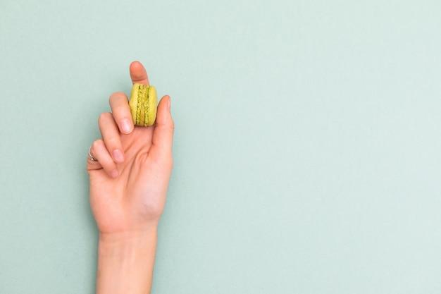 Kobiet ręki trzyma zielonego macaroon tort. widok z góry, leżał płasko. copyspace