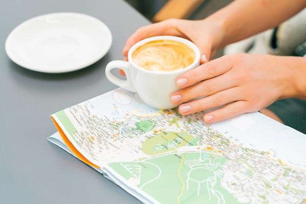 Kobiet ręki trzymają filiżankę kawy nad mapą na stole. dziewczyna podróżuje po wyspach kanaryjskich i szuka nowego miejsca do odwiedzenia. słoneczny dzień w ulicznej kawiarni.