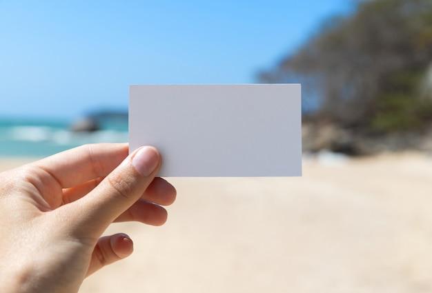 Kobiet ręki trzymającej pusty biały biznes kartkę z życzeniami na lato plaża