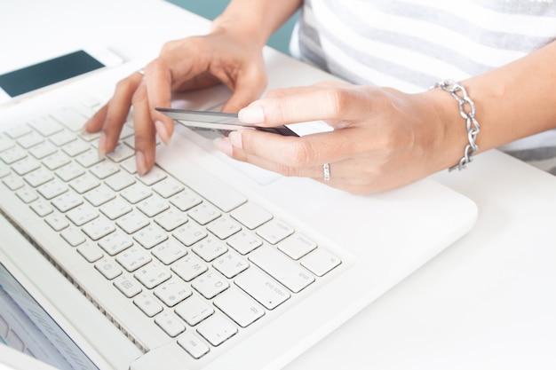 Kobiet ręki używać laptop i kredytową kartę. płatności online, bankowość internetowa