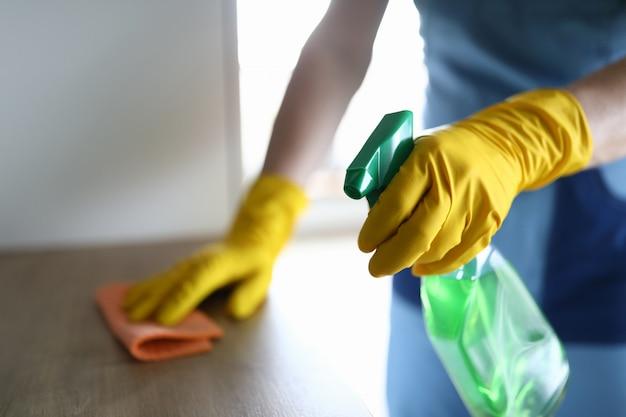 Kobiet ręki w rękawiczkach dezynfekują stół w domu