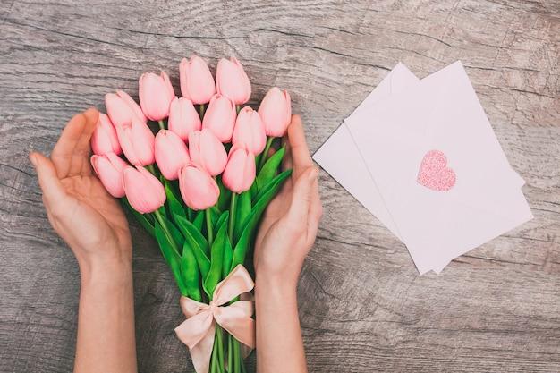 Kobiet ręki z bukietem różowi tulipany i puste białe koperty dla listów, na drewnianym tle.