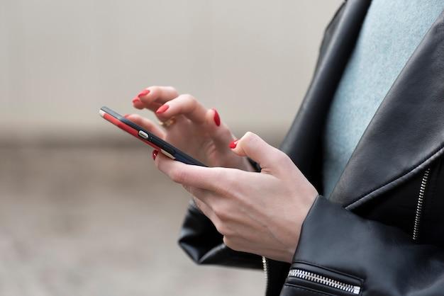 Kobiet ręki z czerwonym manicure'em trzyma smartphone. dziewczyna za pomocą telefonu komórkowego.