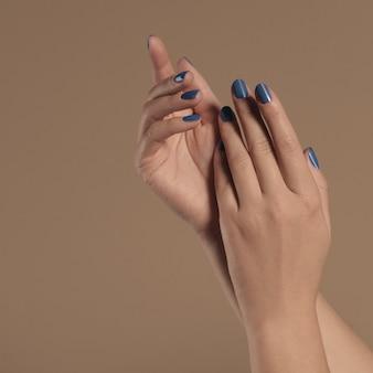 Kobiet ręki z malującymi błękitnymi gwoździami na beżowym tle