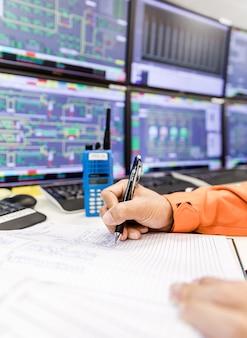 Kobiet ręki z pióra writing na notatniku dla raportowego panelu kontrolnego