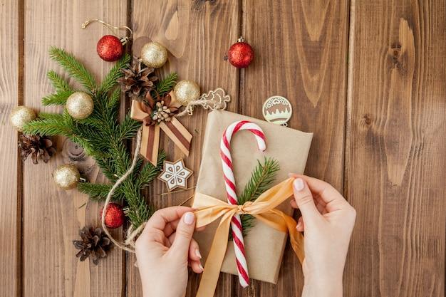 Kobiet ręki zawija bożenarodzeniowego prezent, zamykają up. nieprzygotowane prezenty na drewniane
