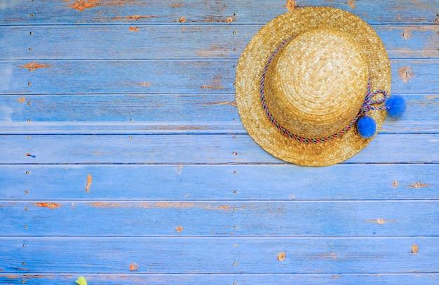 Kobiet słomiany kapelusz na błękitnym drewnianym tle