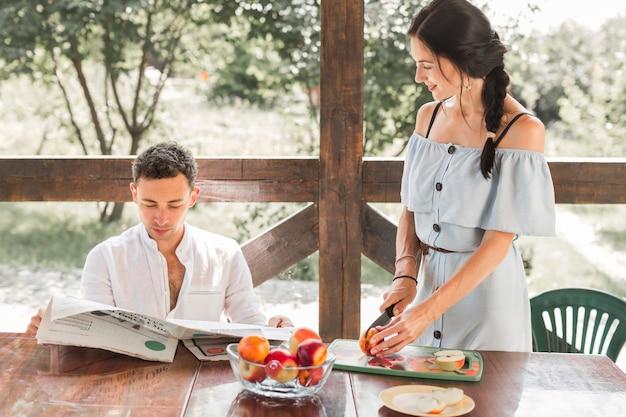 Kobiet tnące owoc patrzeje jej męża czytelniczej gazety