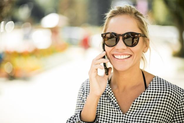 Kobiet uśmiech piękne latarki telefon komórkowy latem