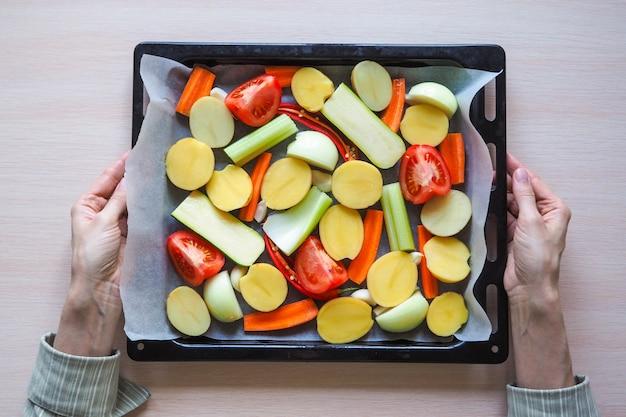 Kobiet w ręce trzyma starą patelnię z warzywami. widok z góry