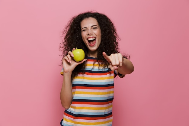 Kobieta 20s z kręconymi włosami uśmiechnięta i trzymająca zielone jabłko odizolowane na różowo