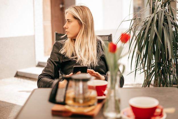 Kobieta 27-30 lat w kawiarni ulicznej przy stole patrzy w bok, pije herbatę, przerwa na kawę