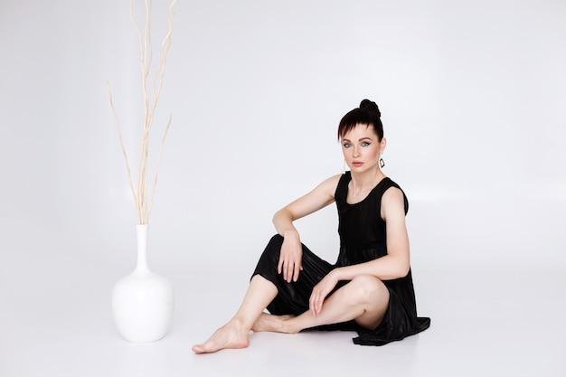 Kobieta 40 lat w czarnej sukni na białym tle