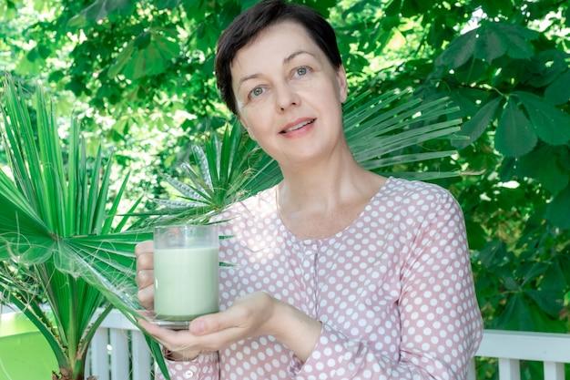 Kobieta 50 plus w średnim wieku trzymać kubek zielony matcha latte kawa herbata szkło szklane liście tropikalny