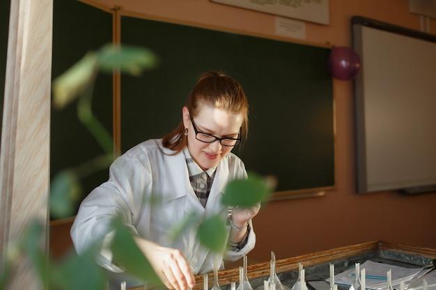 Kobieta absolwent analizuje ziarna na stole do kiełkowania.
