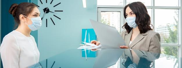 Kobieta administrator w masce ochronnej w białej bluzce pokazuje książeczkę rejestracyjną klientce stojącej w recepcji we współczesnym szpitalnym zbliżeniu