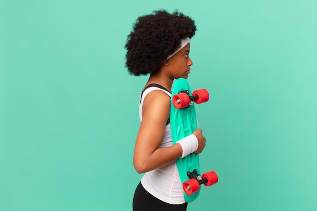 Kobieta afro na widoku profilu, chcąca skopiować przestrzeń do przodu, myśląca, wyobrażająca sobie lub marząca.