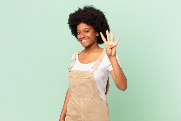 Kobieta afro uśmiechnięta i wyglądająca przyjaźnie, pokazująca numer cztery lub czwarty z ręką do przodu, odliczając koncepcję szefa kuchni