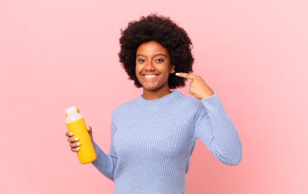Kobieta afro uśmiechnięta pewnie wskazując na swój szeroki uśmiech, pozytywna, zrelaksowana, usatysfakcjonowana postawa. koncepcja smoothie