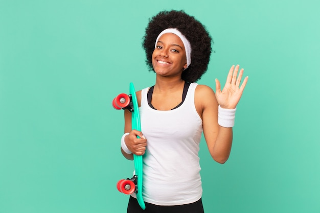 Kobieta afro uśmiechnięta radośnie i radośnie, machająca ręką, witająca i pozdrawiająca cię lub żegnająca. koncepcja deskorolki