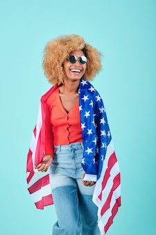 Kobieta afro w swobodnym stroju i okularach przeciwsłonecznych uśmiecha się trzymając amerykańską flagę na na białym tle. dzień niepodległości usa i koncepcja patriotyzmu.