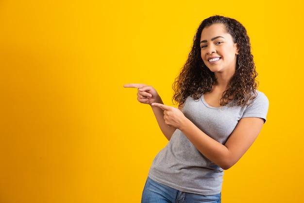 Kobieta afro wskazująca na żółtym tle z miejscem na tekst