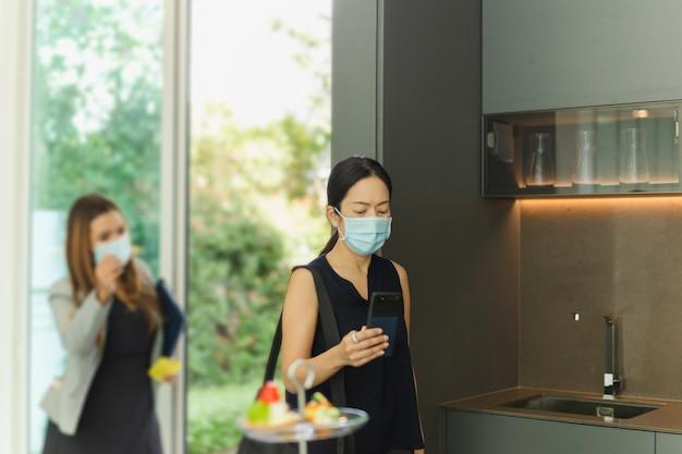Kobieta agent nieruchomości z maską ochronną przedstawiającą potencjalnego kupującego kobietę