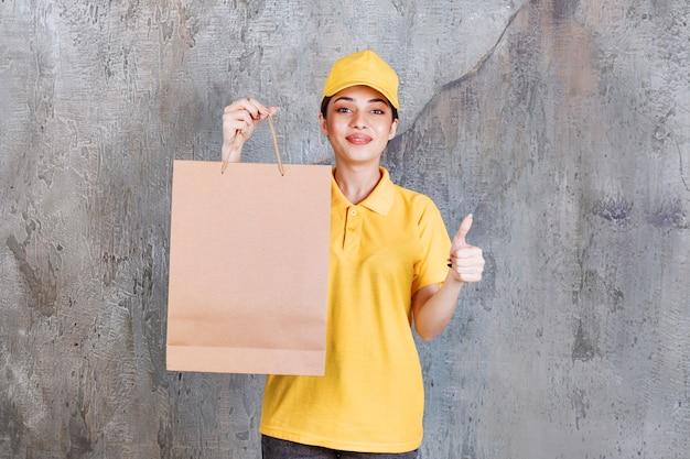 Kobieta agent usług w żółtym mundurze trzyma torbę na zakupy i pokazuje pozytywny znak ręki.