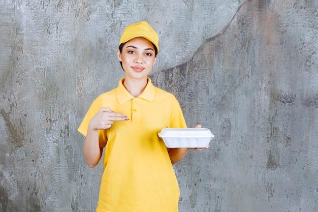 Kobieta agent usług w żółtym mundurze, trzymając plastikowe pudełko na wynos.