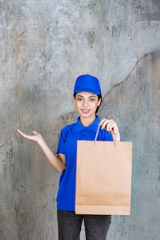 Kobieta agent usługowy w niebieskim mundurze, trzymając kartonową torbę na zakupy.