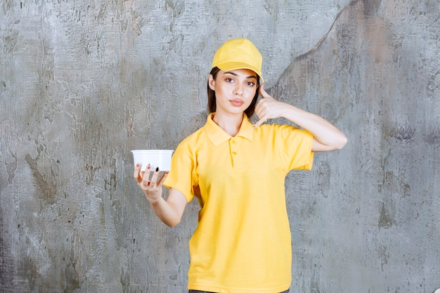 Kobieta agent usługowy w żółtym mundurze, trzymając plastikową miskę na wynos i prosząc o telefon.
