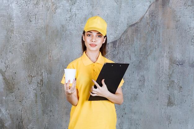 Kobieta agent usługowy w żółtym mundurze, trzymając plastikowy kubek i czarny folder adresowy.