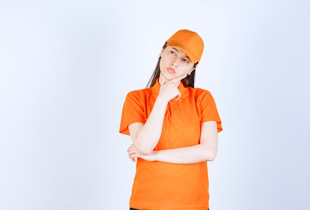 Kobieta agentka nosi strój w kolorze pomarańczowym i wygląda na zamyśloną.