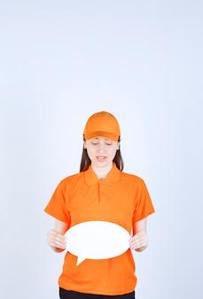 Kobieta agentka w kolorze pomarańczowym, trzymająca owalną tablicę informacyjną