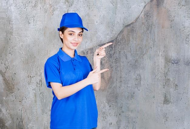 Kobieta agentka w niebieskim mundurze pokazującym prawą stronę