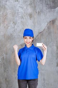 Kobieta agentka w niebieskim mundurze przedstawiając swoją wizytówkę i pokazując znak pozytywnej dłoni.