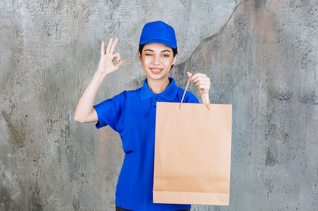 Kobieta agentka w niebieskim mundurze trzymająca kartonową torbę na zakupy i pokazująca pozytywny znak ręki