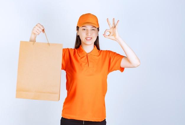 Kobieta agentka w pomarańczowym dresscode trzymająca kartonową torbę na zakupy i pokazująca udany znak ręką oznaczający zapewnienie jakości