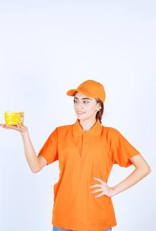 Kobieta agentka w pomarańczowym mundurze trzymająca żółtą filiżankę na wynos