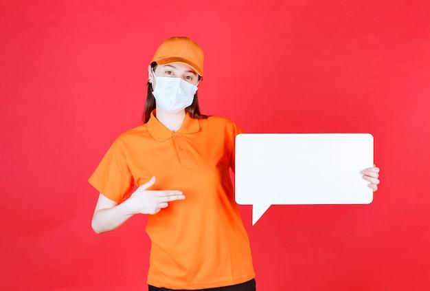 Kobieta agentka w pomarańczowym ubiorze i masce, trzymająca białą prostokątną tablicę informacyjną