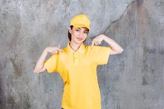 Kobieta agentka w żółtym mundurze stoi na betonowej ścianie i pokazuje się.