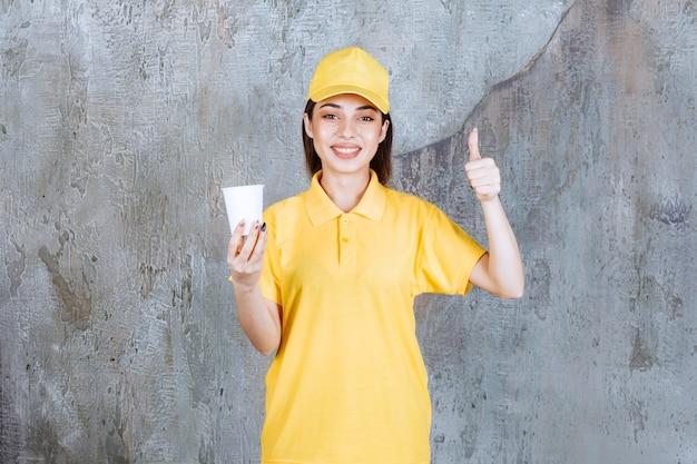 Kobieta agentka w żółtym mundurze trzyma plastikowy kubek i pokazuje pozytywny znak ręki.