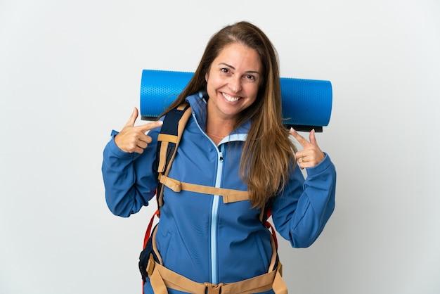 Kobieta alpinista średnim wieku z dużym plecakiem, dając kciuki do góry gestowi