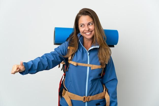 Kobieta alpinista średnim wieku z dużym plecakiem na białym tle, dając kciuk w górę gestu