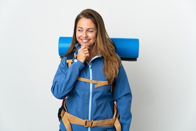 Kobieta alpinista średnim wieku z dużym plecakiem na białym tle patrząc z boku i uśmiechnięty