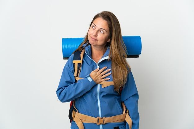 Kobieta alpinista średnim wieku z dużym plecakiem na izolowanej ścianie patrząc w górę, uśmiechając się